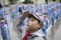 "Students attending the flag-raising ceremony at the Yang Dezhi ""Red Army"" elementary school in Wenshui, Xishui country in Guizhou province. Photo: AFP"