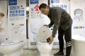 Zhong Jiye, a co-founder of Shenzhen Trump Industrial Co pictured with one of the firm's Trump-branded toilets. Photo: AP