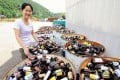 A resident of Kamikatsu shows off recycling bins for brown glass bottles, one of 45 categories into which residents sort their garbage. Photo: YouTube / Seeker Stories