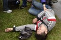 An injured man lies on the ground after clashes between pro-independence and pro-unification groups during the 70th anniversary of the 228 incident at the Chiang Kai-shek Memorial Hall in Taipei on Tuesday. Photo: AFP