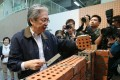 Chief Executive candidate John Tsang tries his hand at brick laying during a training open day in Sheung Shui. Photo: Dickson Lee
