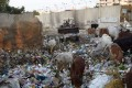A Pakistani municipal worker dumps rubbish in a residential area of Karachi. Photo: AFP
