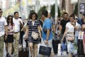 A group of Chinese tourists carry shopping bags and suitcases in the Ginza district of Tokyo. Photo: Bloomberg