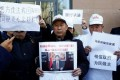 Relatives of passengers aboard Malaysia Airlines flight MH370 hold up placards as they wait to speak to a government official outside the foreign ministry in Beijing. Photo: Reuters