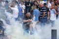 An England fan evades a smoke grenade thrown by riot French police during clashes with Russian supporters. Photo: EPA