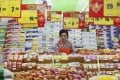 An employee arranges stock under price tags at a supermarket in Huaibei, Anhui province. Photo: Reuters