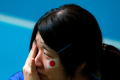 A Japanese soccer fan wipes her tears as Japan loses their 2014 World Cup soccer match against Colombia, at a public viewing event in Tokyo. Photo: Reuters/Issei Kato