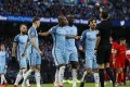 Manchester City players surround the referee after the awarding of a penalty to Liverpool during Sunday's 1-1 draw. Photo: Reuters