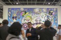 Visitors to Art Basel Hong Kong view a painting by Tan Tan Bo. Dealers report fewer collectors from China at the fair than last year. Photo: May Tse