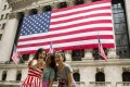 Chinese tourists take photos outside the New York Stock Exchange. Visa applications may get tougher for many mainlanders. Photo: Reuters