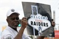 An Oakland Raiders fan displays a sign to passing motorists on the Las Vegas Strip near the 'Welcome to Fabulous Las Vegas' sign after NFL owners voted to approve the relocation. Photo: AFP
