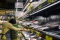 Supermarket employees cleared shelves of Brazilian meat products. Photo: AFP