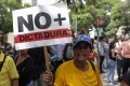 A woman carries a sign that reads 'No Dictatorship' during a protest in Caracas, Venezuela, as several protests broke out after a Supreme Court ruling took power from congress raising fear of a dictatorship. The ruling is being condemned by opponents of President Nicolas Maduro and foreign governments. Photo: EPA