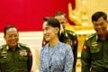 Aung San Suu Kyi smiling in front of military generals in 2016. Photo: AFP