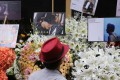 A fan of late Canto-pop singer Leslie Cheung looks at the wreaths and messages left in memory of the singer/actor outside the Mandarin Oriental Hong Kong hotel in Central last week. Photo: Sam Tsang