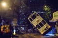Emergency service personnel watch as a double-decker tram is lifted back up by crane after it tipped over on a main road in Hong Kong on Thursday. Photo: AFP