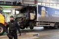 Tow trucks move the beer truck that crashed into the Ahlens department store after ploughing down Drottninggatan Street in central Stockholm, Sweden. Photo: EPA