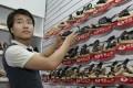 A Chinese salesman adjusts a display as he waits for customers at his shoe shop in Kampala, Uganda. Photo: AP