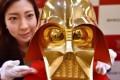 An employee of Japan's jeweller Tanaka Kikinzoku Jewellery displays a pure gold life size mask of Darth Vader. Photo: AFP