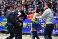 A supporter of the LGBT community carrying a rainbow flag approaches presidential candidate Moon Jae-in. Photo: EPA
