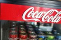 A Coca Cola sign is seen as Coke products are on display in a store as the company announces plans to cut 1200 corporate staff jobs. The announced changes come as the company battles a slide in soda sales which along with higher costs has lead to a 20 per cent drop in quarterly profit. Photo: AFP
