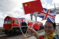 Chinese women wave flags at the official ceremony earlier this month to mark the departure of the first UK-to-China freight train, laden with containers of British goods, from the DP World London Gateway, in Stanford-le-Hope, east of central London. Photo: Reuters