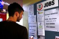 A man uses his phone to record job ads posted on a noticeboard at a backpacker hostel in Sydney last May. Photo: Reuters