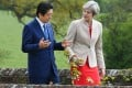 Japanese Prime Minister Shinzo Abe and his British counterpart Theresa May stroll through the garden at the British prime minister's country residence. Photo: Kyodo