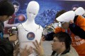 Chinese students work on a humanoid robot designed by them with funding from a Shanghai investment company, at the World Robot Conference in Beijing, last October 21. Photo: AP