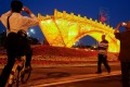 """People take pictures of the """"Golden Bridge on Silk Road"""" art installation, set up ahead of the belt and road forum in Beijing this weekend. The forum has an emphasis on mutual discussion, mutual construction and mutual sharing. This is greatly welcomed. Photo: Reuters"""