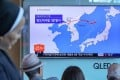 Passengers watch a news report on North Korea's missile test at a railway station in Seoul on Sunday. Photo: Reuters