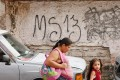 Local residents pass by grafitti made by the Mara Salvatrucha gang in the MS-13-controlled El Bosque neighborhood in Tegucigalpa. Hundreds of people are fleeing due to gang violence in Honduras. Photo: AFP