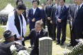 South Korean President Moon Jae-in consoles family members of the deceased in front of a grave marker during the 37th annual May 18 Democratic Uprising memorial at the Gwangju National Cemetery. Photo: AP
