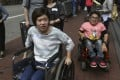 Writer Rachel Cheung and photographer Kevin Cheung try to complete the wheelchair challenge around Wan Chai. Photo: Xiaomei Chen