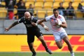 England's Dan Norton is chased by New Zealand's DJ Forbes with empty seats in the background at the 2017 Wellington Sevens. Photos: AFP