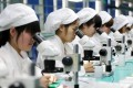 A file picture of workers assembling mobile phone parts at a factory in Anhui province. Photo: EPA