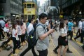 Pedestrians cross a road in Central. A survey last year found that four in 10 Hongkongers wanted to leave the city. Photo: EPA