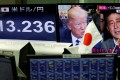 US President Donald Trump and Japanese Prime Minister Shinzo Abe seen on a TV monitor as the one next to it shows the yen's exchange rate against the US dollar, at a forex trading company in Tokyo on February 1. Photo: Reuters