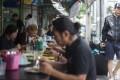 A tourist walks next to a street food stall in Bangkok, Thailand. Photo: EPA