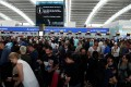 People wait with their luggage at the British Airways check-in desks at Heathrow Terminal 5 in London. Photo: Reuters