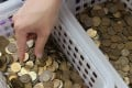 Staff at the Hong Kong Monetary Authority with baskets of old coins. Photo: May Tse
