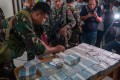 Soldiers present money reportedly recovered from a gunner's post in Marawi. Photo: EPA
