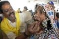 """An Indian member of the Bathini Goud family administers the """"fish medicine"""" to a Lambadi tribal woman. Photo: AFP"""