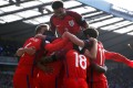 England's Harry Kane is mobbed by teammates after netting a late equaliser. Photo: Reuters