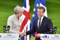 Britain's Prime Minister Theresa May (L) and France's President Emmanuel Macron shake hands during a joint press conference in the grounds of The Elysee Palace in Paris on June 13, 2017. Photo: AFP