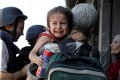 A girl cries as her parents are interviewed by media after displaced civilians are rescued by Iraqi security forces from the bitter fighting in the Old City of Mosul, Iraq, on Friday, June 23, 2017. Photo: Reuters