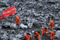 """Rescue workers search for survivors at the landslide site. The banner reads """"Chengdu fire department rescue team"""". Photo: Reuters"""