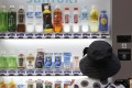 A woman purchases a Suntory beverage from a vending machine in Tokyo. File photo: Reuters