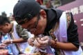 Contestants get stuck in at the insect eating challenge in Lijiang, Yunnan province, on Sunday. Photo: Handout