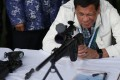 Philippine President Rodrigo Duterte checks the scope of a Chinese-made CS/LR4A sniper rifle during the ceremonial presentation weapons by China to the Philippines Wednesday. Photo: AP